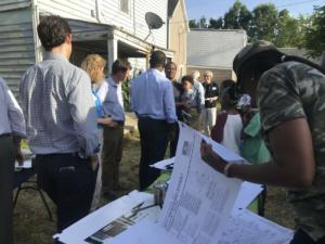Neighbors look at building plans at neighborhood meet and greet.